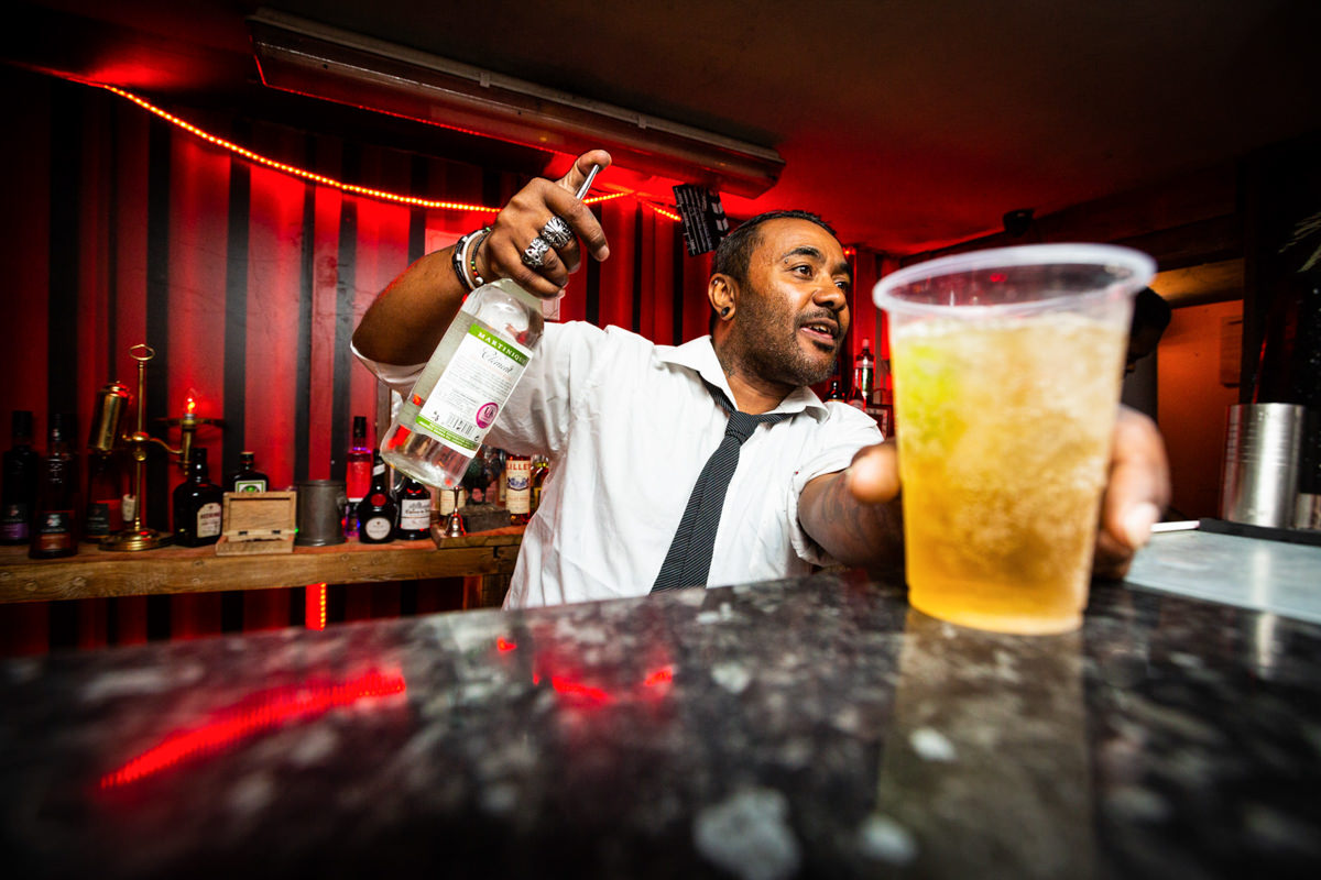 man at bar with bottle of spirits malice london