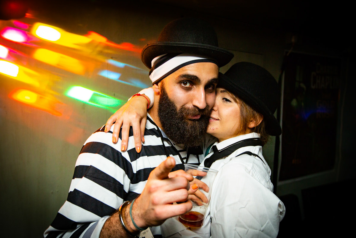 man and woman in bowler hats hugging at party