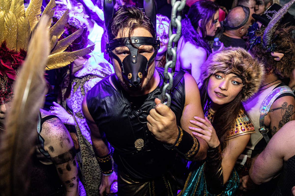 man in leather mask holding chain at fox and badge party