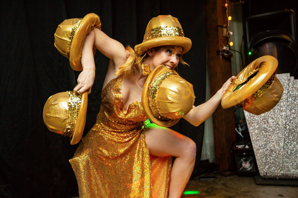 woman with five gold hats performing at malice arts london