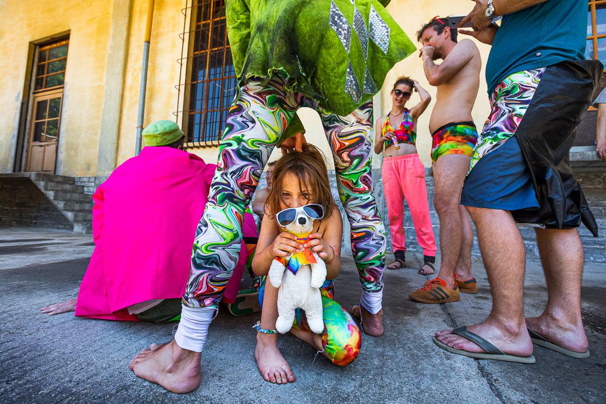 girl with teddy bear inbetween adults legs