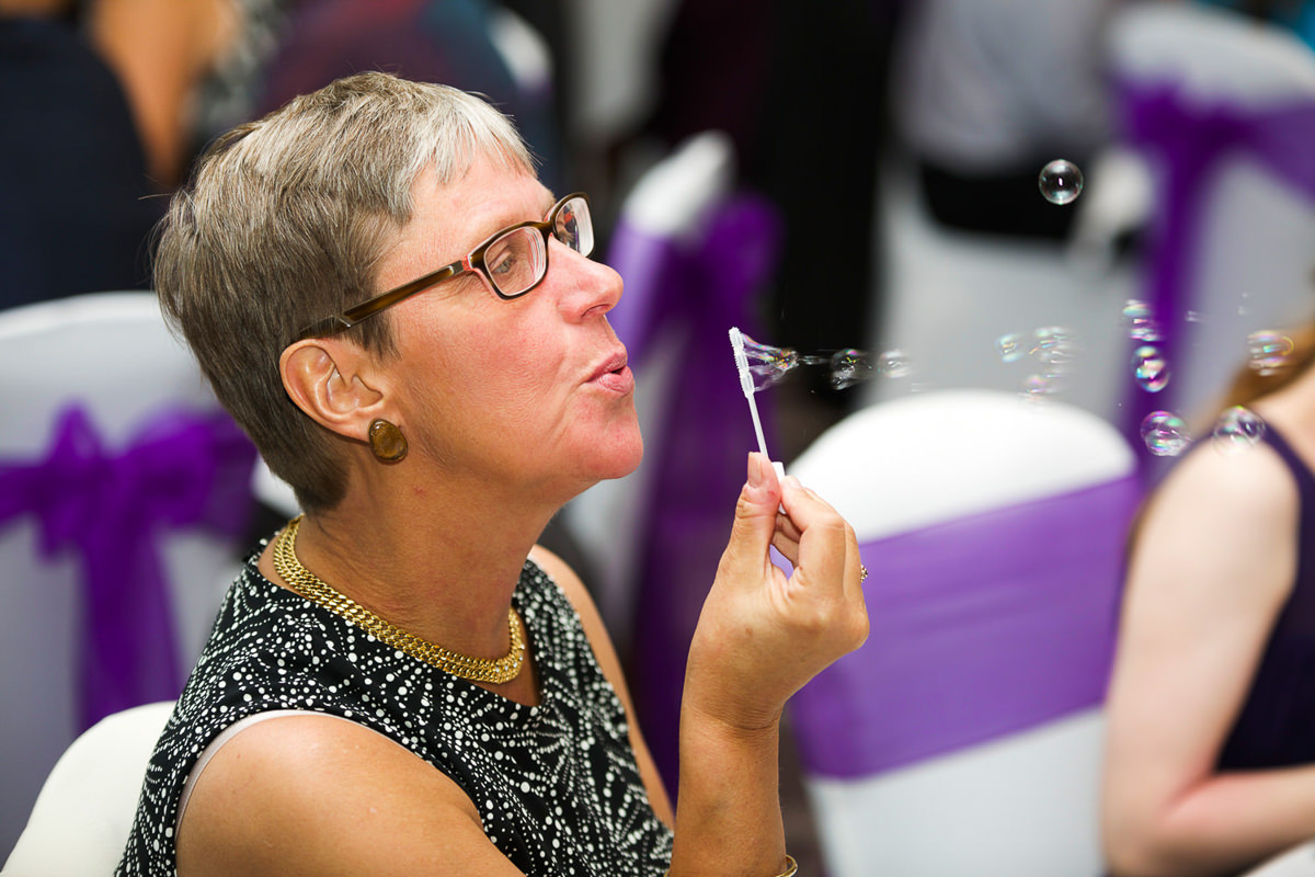 woman blowing bubbles wedding photography