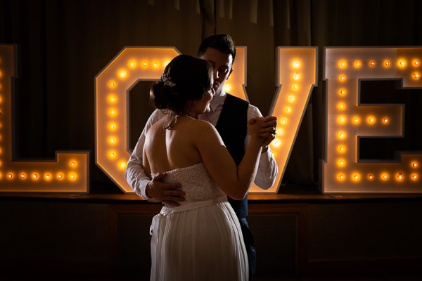 woman and man first dance in front of love sign