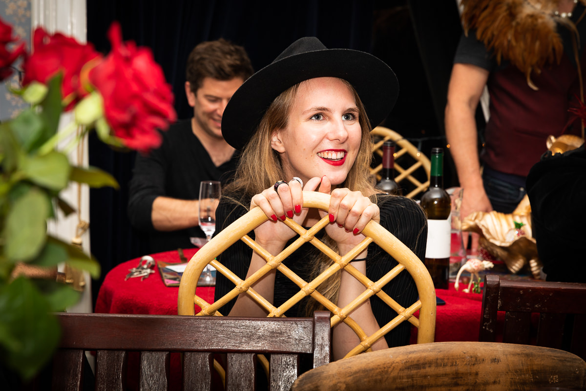Womain in black hat holding chair
